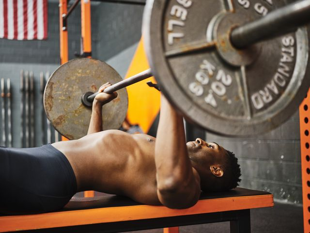 man working out in a gym with barbell and weights