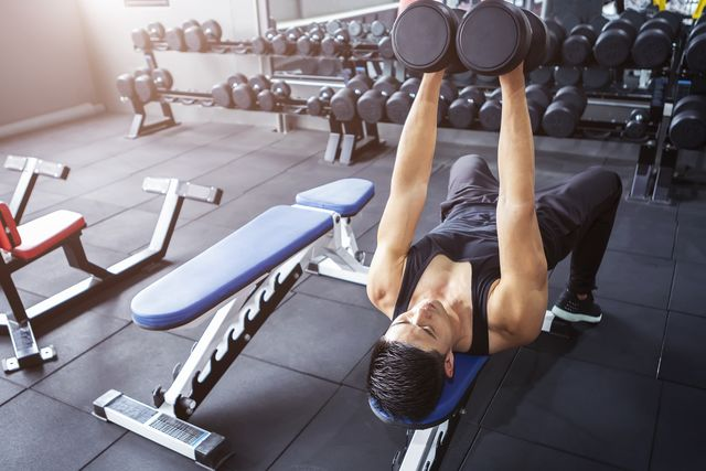 a man workout with dumbbell at gym