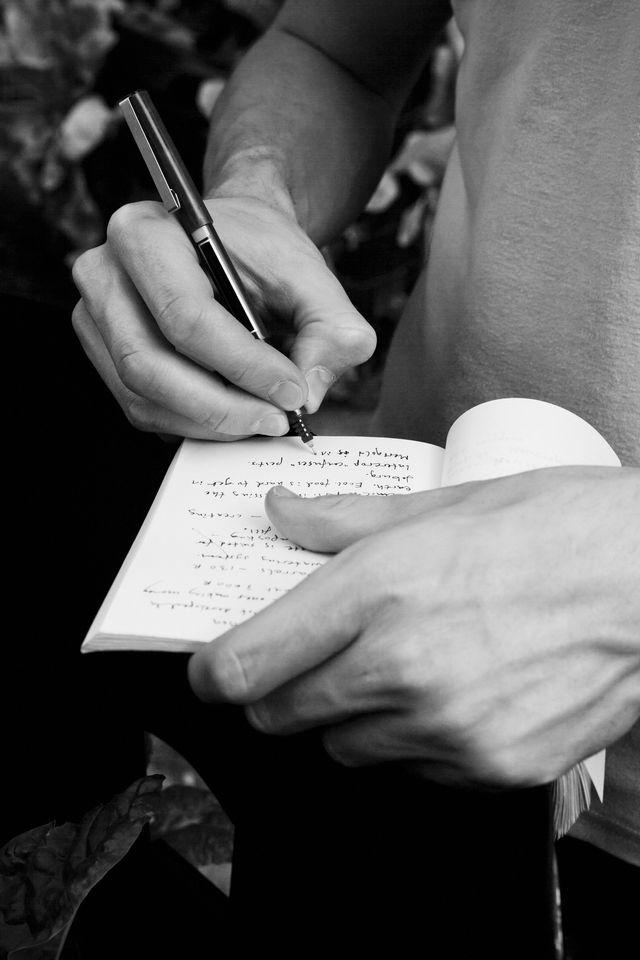 man writing on diary