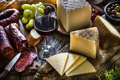 Spanish food: Manchego cheese, spanish chorizo and red wine on rustic wooden table