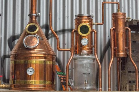 A still or distillery equipment made from copper at a gin manufacturer in central london. Micro breweries and distilling gin with basic kit and gear.