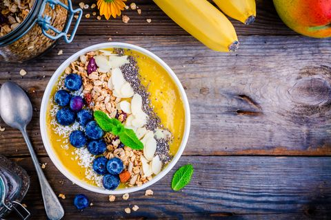 Mango smoothies bowl with blueberries, granola, chia seeds and almonds