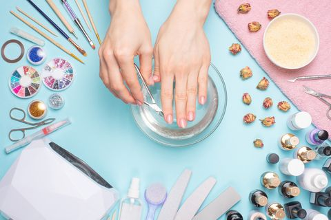 Manicure - tools for creating, gel polishes, all for nail care, beauty and care concept. On a blue background, hands with a manicure