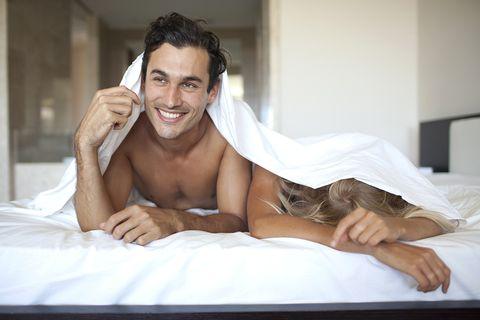 Stel in bed terwijl de man opkijkt