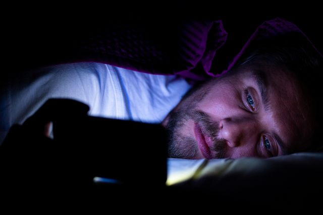 bearded young man is lying in bed under his blanket he cannot sleep and is watching something on his mobile phone