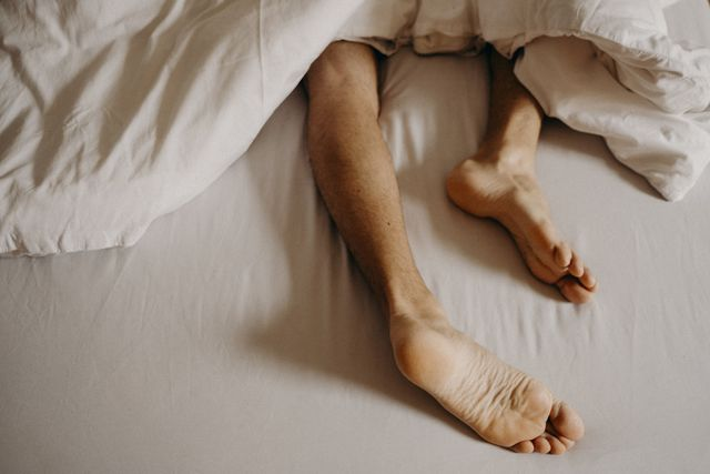 man´s feet resting in bed