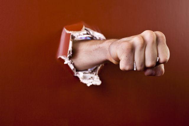 man's fist coming through wall