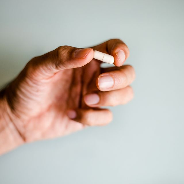 A man's hand holding a capsule / pill