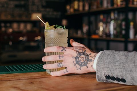 mans hand reaching for a cocktail in a bar