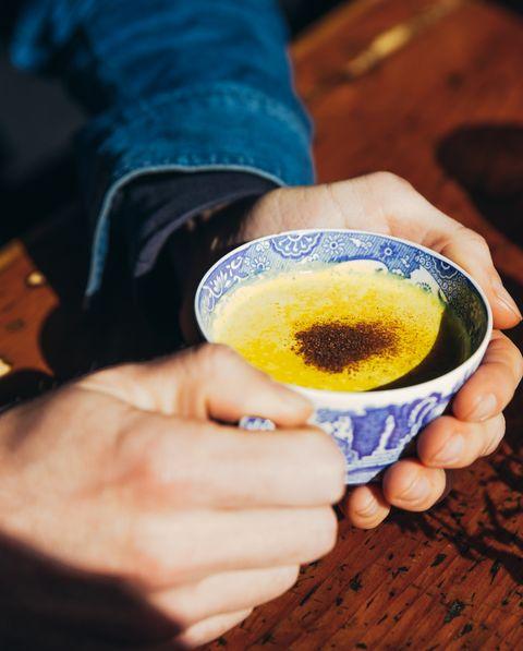 Mans hands holding golden milk