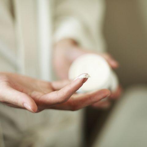 Man's hands holding jar of moisturizer, close-up