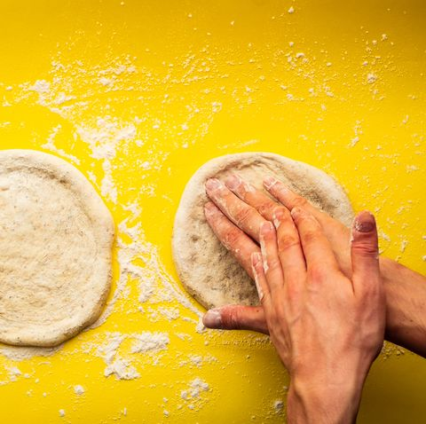 man's hands kneading a homemade pizza dough on a yellow background full of flour