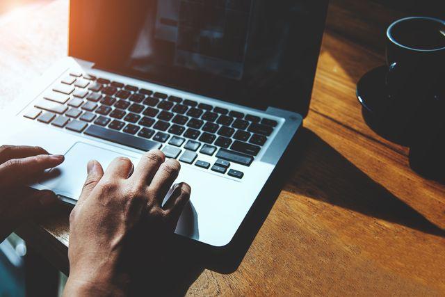 man's hands using laptop