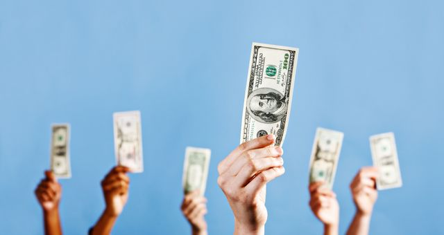 many mixed hands hold up us dollars against blue