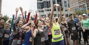Marathon runners posing, waving and cheering for selfie at starting line on urban street