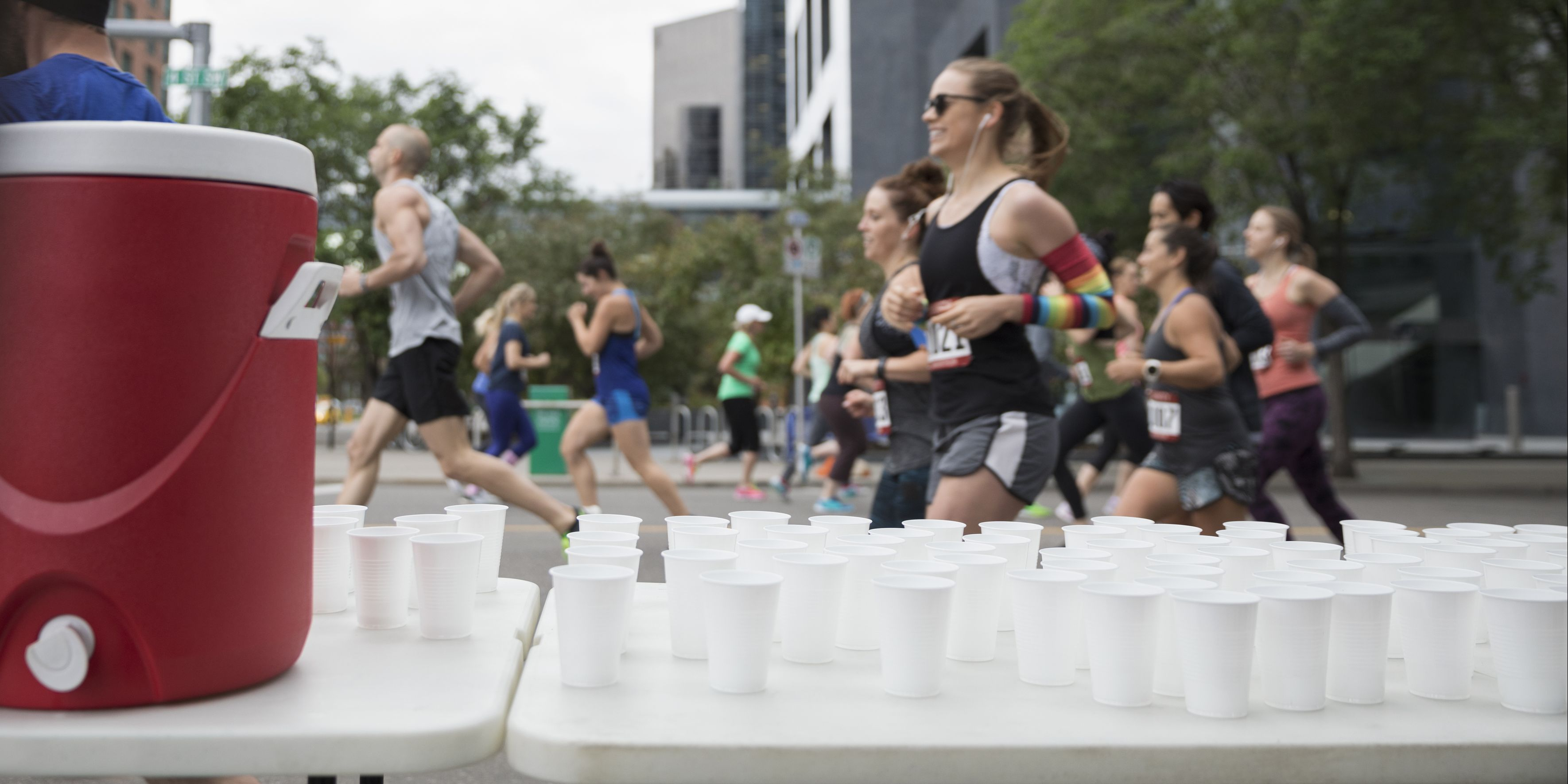 Marathon runners running, passing water station on urban street