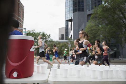 Marathon runners running, passing water station on urban street