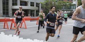 Marathon runners running, turning corner at water station on urban street