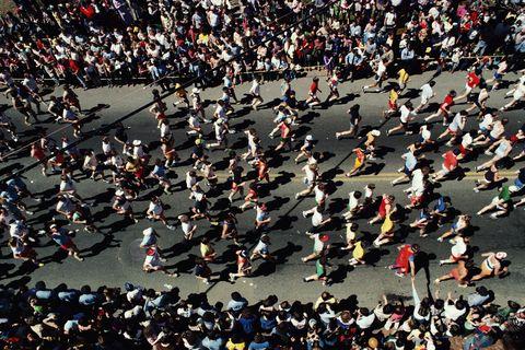 Marathoners running on urban street, elevated view
