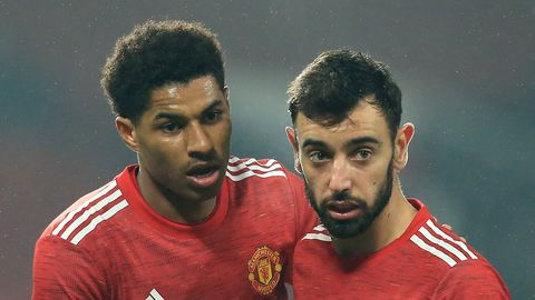 manchester united players marcus rashford and bruno fernandes hug each other as they celebrate a goal during a premier league football game