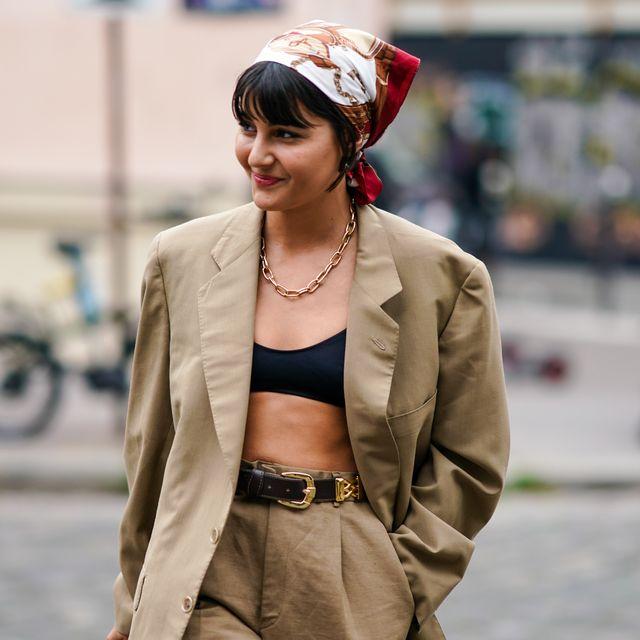 maria bernad draagt carre sjaal om haar hoofd gecombineerd met en beige pak en zwarte bralette tijdens fashion week in parijs