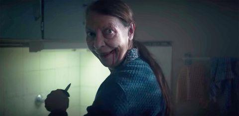 una anciana con un cuchillo y sangre en la boca
