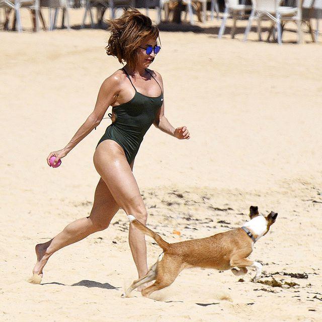 maría patiño, en bañador, juega con su perrita beige en las playas de fuerteventura