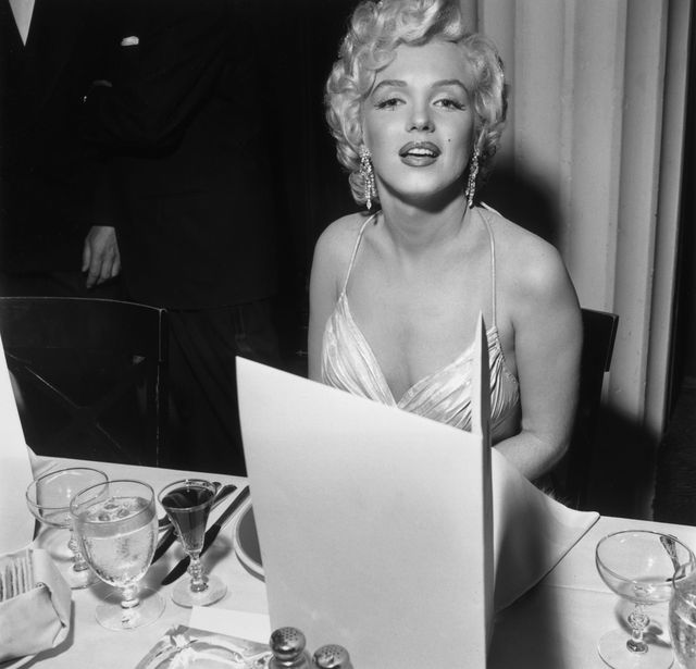circa 1952  exclusive american actor marilyn monroe 1926   1962 sits at a banquet table during a party for studio executive darryl f zanuck in the hollywood hilton, hollywood, california, early 1950s monroe is wearing a pleated dress with spaghetti straps  photo by m garrettmurray garrettgetty images