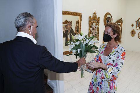 el ex banquero le entrega un ramo de lirios blancos a su novia tras su exposición