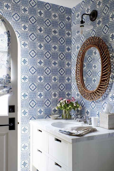 blue and white tile in a bathroom that has a round mirror over a marble top white vanity