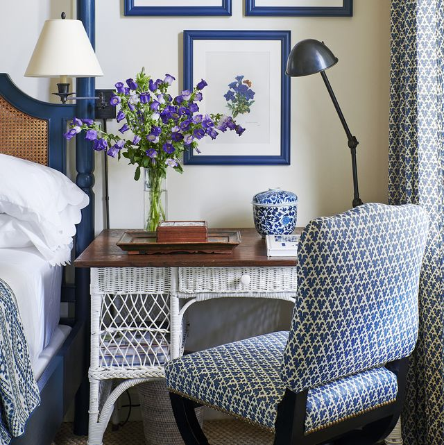 a white wicker desk with a wood top sits by a bed and has four botanicals hanging over it and the room has blue and white decor