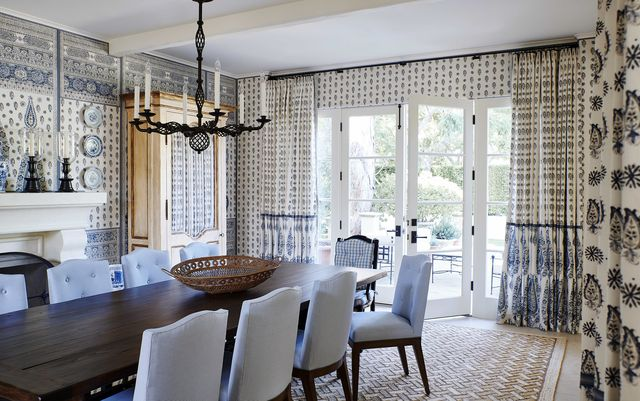 a blue and white dining room has doors open to the outdoors