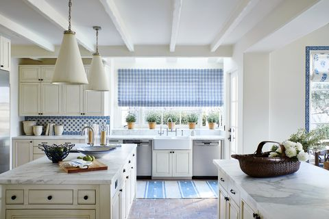 an off white kitchen with blue and white backsplash and rug and window treatment