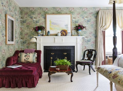 a plum velvet chaise sits snugly in the corner of a bedroom next to a fireplace
