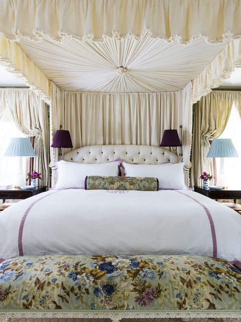 a grand caopy bed with white and lilac personalized bedding and a floral bench at the end