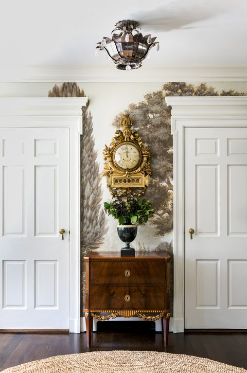 two tall white wood doors flank an antique chest and a clock from 1780 hangs above