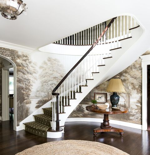 a sweeping staircase in an entry with a sepia toned mural on the curved walls