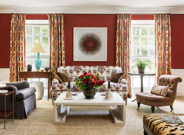 brick red walls with two windows that frame a patterned sofa with a coffee table and two chairs