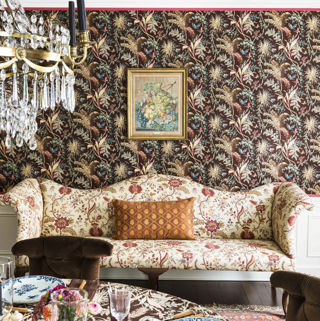 a patterned sofa sits against a wallpapered wall in the dining room
