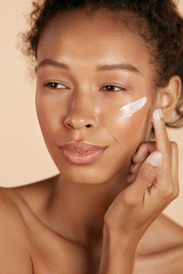 face skin care woman applying cosmetic cream on clean hydrated skin portrait beautiful happy smiling african americangirl model with natural makeup applying facial moisturizer, beauty product