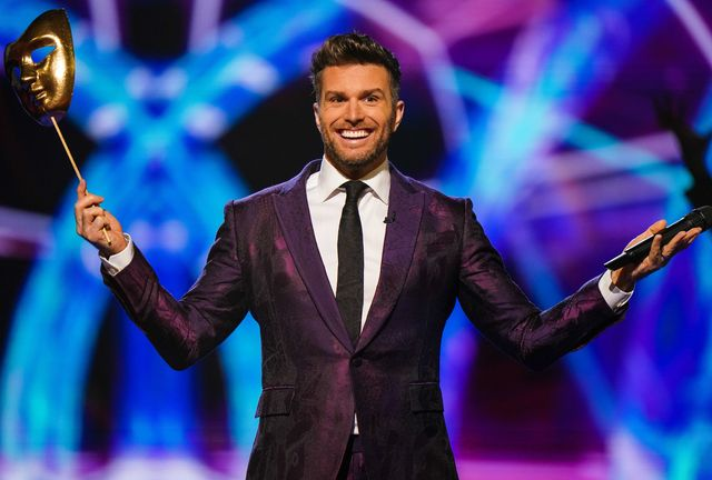 the masked dancer host joel dommett on stage, holding a gold theatre style face mask on a stick in his right hand and his microphone in his left hand