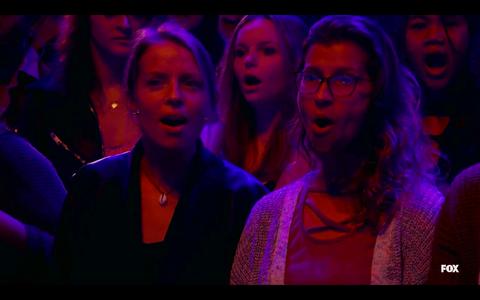 зрители смотрят запись певца в маске