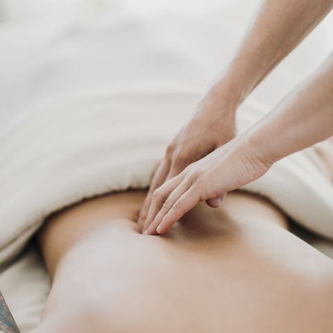 a massage therapist works on a female patient's back