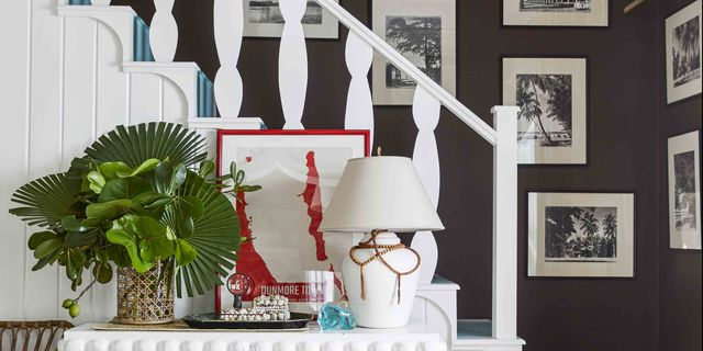 a stairwell painted white with a white table and a gallery wall in the backgroun
