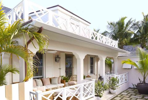 a shell pink cottage in a tropical setting with white chippendale railings