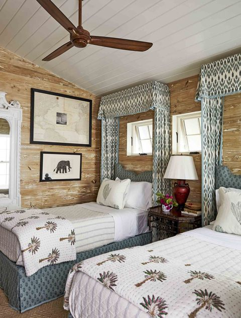 limed pecky cypress paneling envelops the walls in the guest cottage with two twin beds