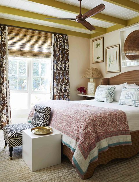 master bedroom beams are painted a brilliant chartreuse and the bed linens and window coverings are full of pattern