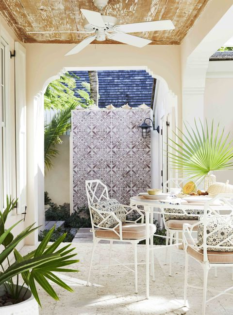 the outdoor shower's portuguese cement tilework reads like antique wallpaper against the white outdoor dining furnture