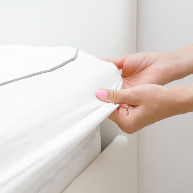 woman pulling mattress protector over bed