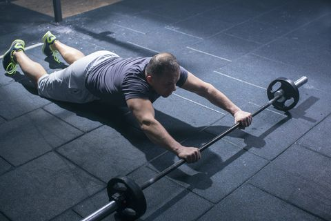 Mature athlete man doing exercise with weights in gym